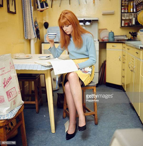 English actress Jane Asher drinks from a cup whilst reading papers in her kitchen in London in 1966