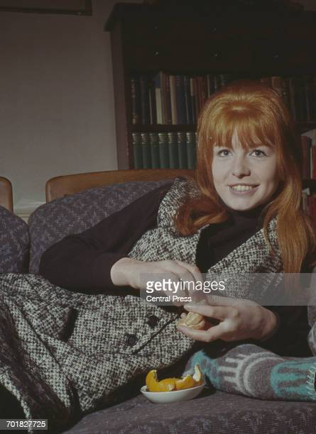English actress Jane Asher peeling an orange at home 1964