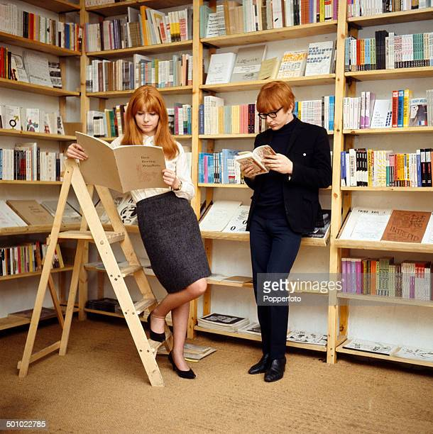 English actress Jane Asher reads books with her brother musician Peter Asher in a library in 1966