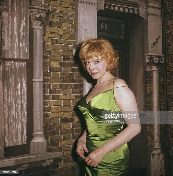 English actress Janet Munro pictured wearing a green satin dress on a film set in front of a backdrop depicting a Victorian terraced house in 1962