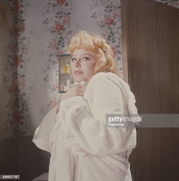 English actress Janet Munro pictured wearing a white towelling robe on a film set in 1962