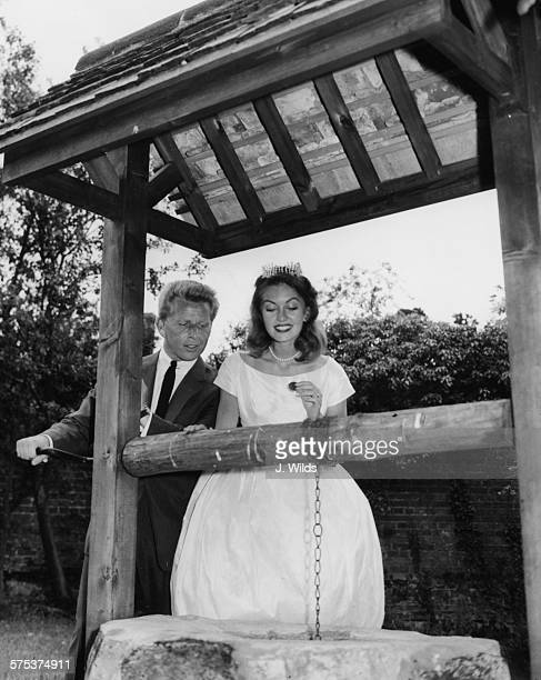 English actress Janette Scott and her new husband Canadian singer Jackie Rae pictured dropping coins in to a wishing well on their wedding day in the...