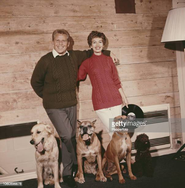 English actress Janette Scott pictured with her husband Canadian singer Jackie Ray and four dogs at home in England in October 1960