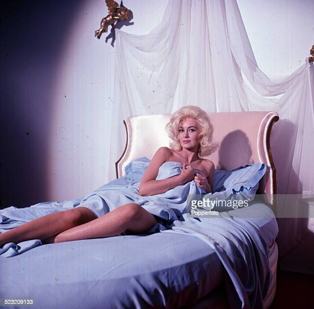 English actress Janette Scott posed lying on a bed covered with a blue sheet on the set of the film 'The Beauty Jungle' in 1963