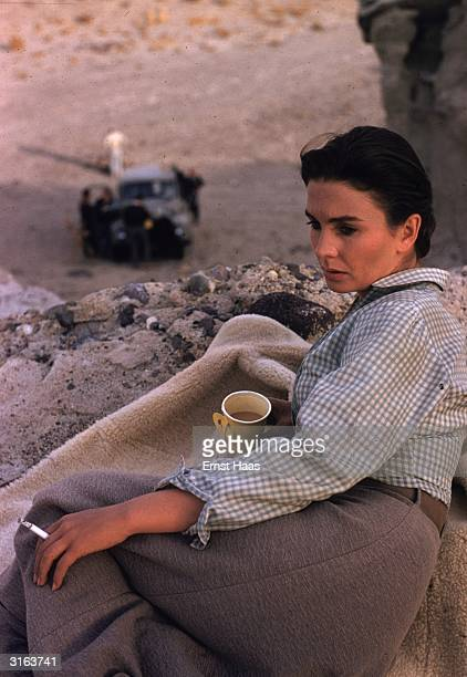 English actress Jean Simmons finds a secluded spot for a quiet smoke during the filming of the William Wyler western 'The Big Country'