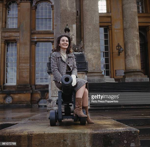 English actress Jean Simmons pictured sitting on top of a cannon beside steps leading up to the front entrance of Blenheim Palace in Woodstock...