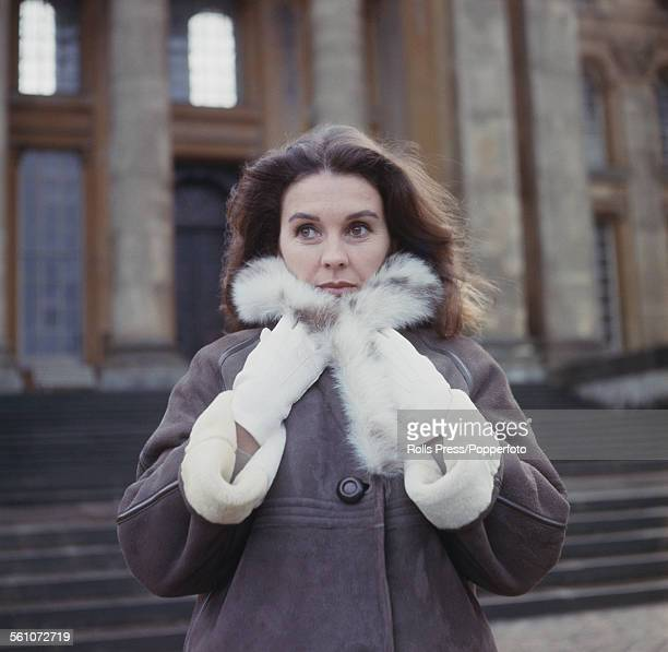 English actress Jean Simmons pictured wearing a shearling coat whilst standing on the steps in front of the entrance to Blenheim Palace in Woodstock...
