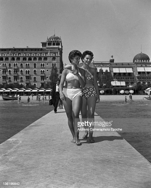 English actress Jean Simmons wearing a swimming suit walking on the beach outside the Excelsior Hotel Venice 1950