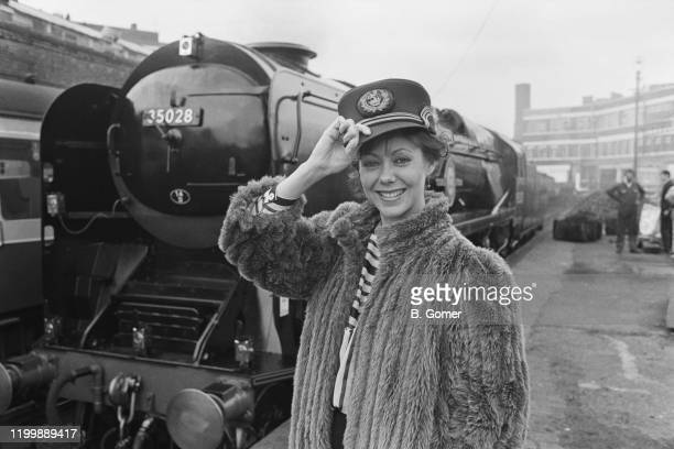 English actress Jenny Agutter wearing a railwayman's cap and posing in front of the Merchant Navy 4-6-2 class steam locomotive, 35028 Clan Line, 1st...