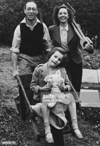 English actress Jessie Matthews and her husband actor Sonnie Hale in their garden of their home in Hampton UK with their daughter Catherine 12th May...