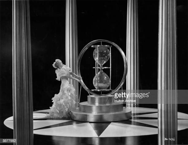 English actress Jessie Matthews dances round a large hourglass in a scene from the film 'Evergreen' directed by Victor Saville for Gaumont