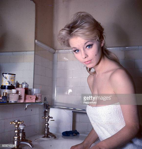 English actress Jill Haworth posed standing at a sink wearing a white bath towel in 1963