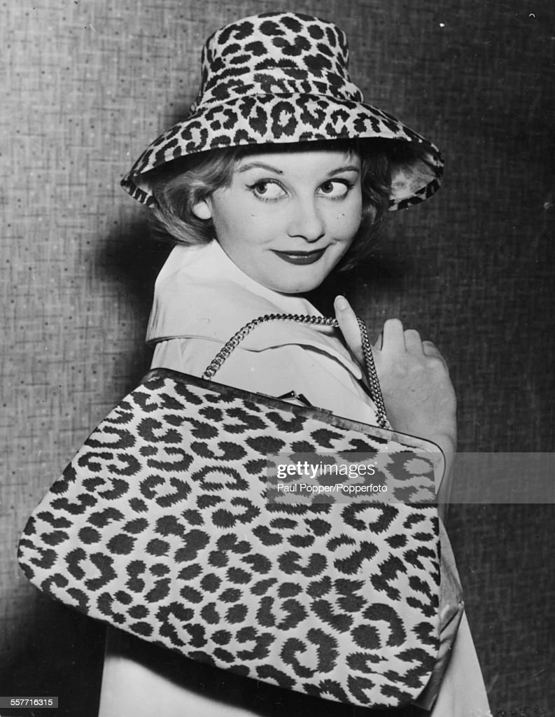 English actress Jill Ireland (1936-1990) wearing a leopard print hat and carrying a matching handbag as she attends a fashion show in London, circa 1960.