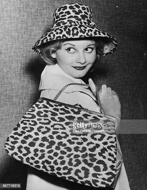 English actress Jill Ireland wearing a leopard print hat and carrying a matching handbag as she attends a fashion show in London, circa 1960.