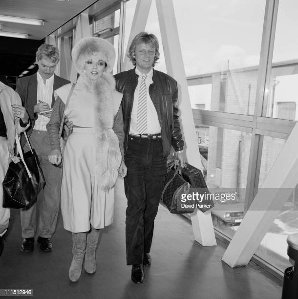 English actress Joan Collins at a London airport with her fiance Swedish pop singer Peter Holm 21st October 1984