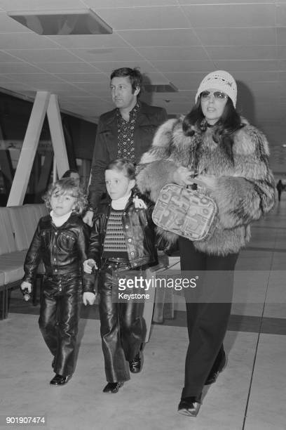 English actress Joan Collins leaves London Airport for Los Angeles with her partner Ron Kass and children Sacha and Tara 30th December 1971 She is...