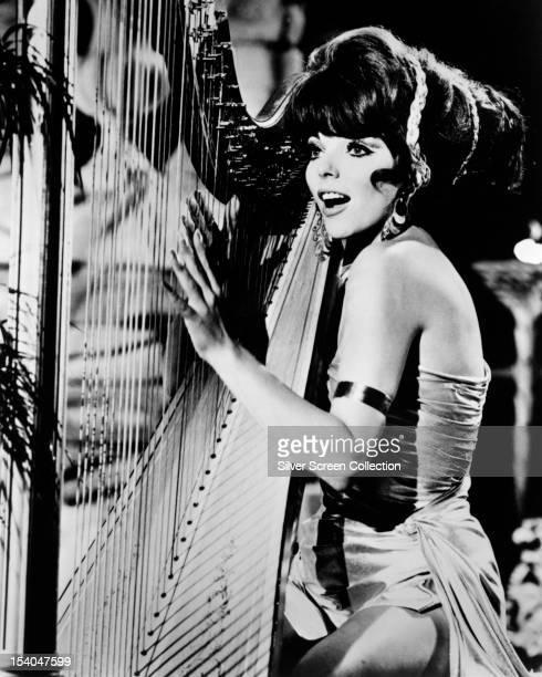 English actress Joan Collins playing a harp as Lorelei Circe aka Siren in the American TV series 'Batman' 1967