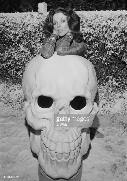 English actress Joan Collins poses with a huge model skull during the making of anthology horror film 'Tales From the Crypt' at Shepperton Studios UK...