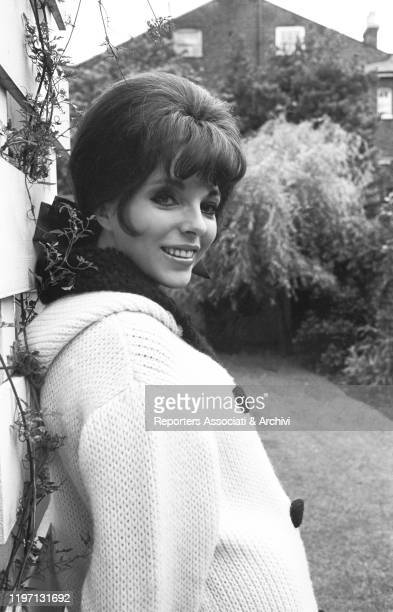 English actress Joan Collins posing smiling in the garden of her house in London London 2nd July 1964