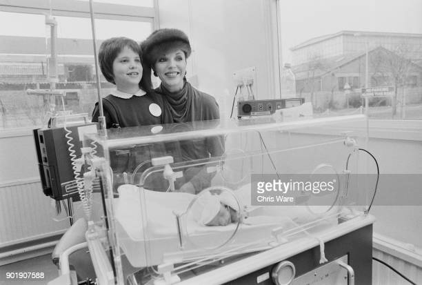 English actress Joan Collins shows her daughter Katyana an incubator at the Central Middlesex Hospital in London 15th December 1980 Collins presented...
