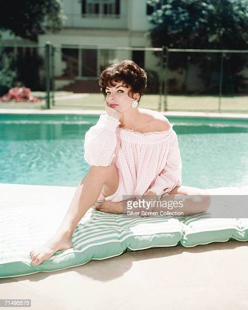 English actress Joan Collins sits on a mattress by a swimming pool circa 1960