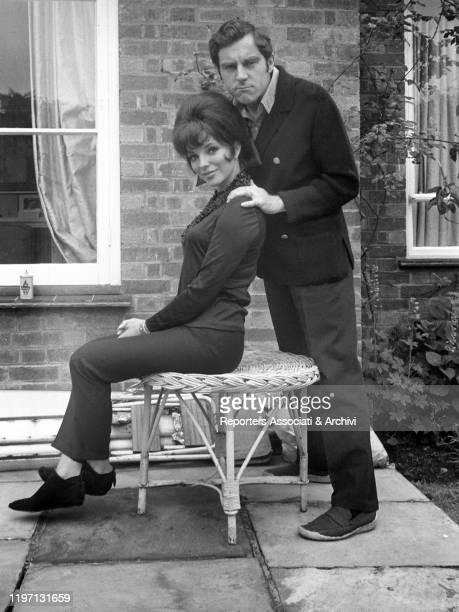 English actress Joan Collins sitting on a stool in the garden of her house in London and posing with her husband and English actor Anthony Newley...