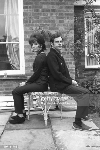 English actress Joan Collins sitting on a stool with her husband and English actor Anthony Newley in the garden of their house in London London 2nd...