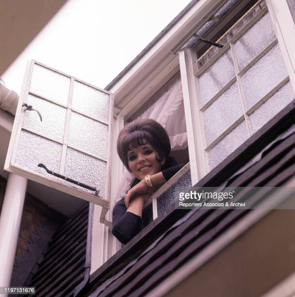 English actress Joan Collins smiling at the window of her house in London London 2nd July 1964
