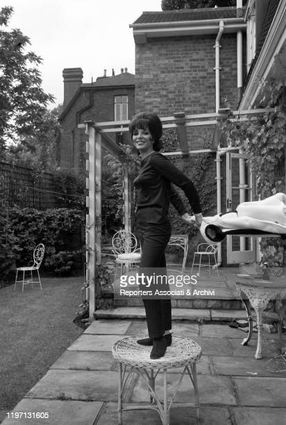 English actress Joan Collins standing on a stool in the garden of her house in London London 2nd July 1964