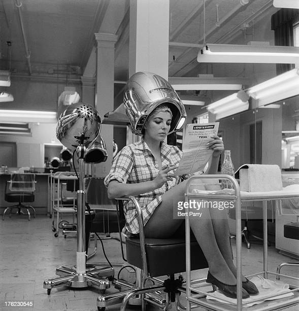 English actress Joan Collins waits for her hair to dry in a film studio 15th August 1955