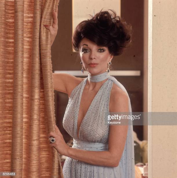 English actress Joan Collins wearing a halter neck dress decorated with sequins