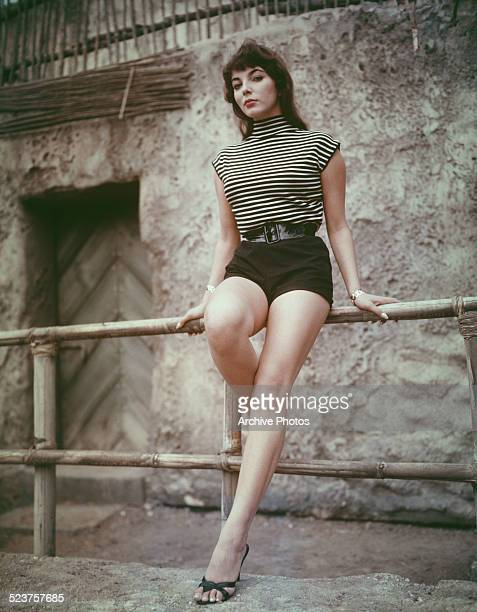 English actress Joan Collins wearing a striped top and shorts circa 1955