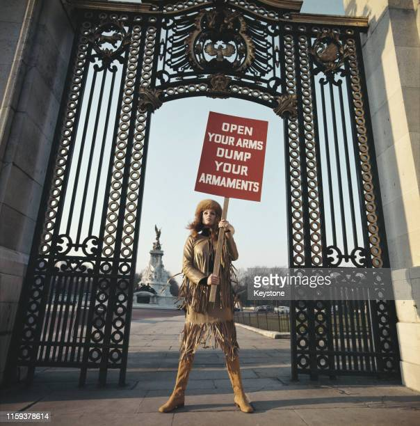 English actress Joanna Lumley outside Buckingham Palace in London with a placard reading 'Open Your Arms Dump Your Armaments' circa 1970