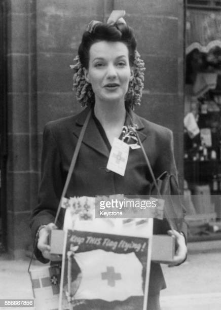 English actress Judy Campbell selling flags on Flag Day in the West End of London during World War II, 22nd June 1942.