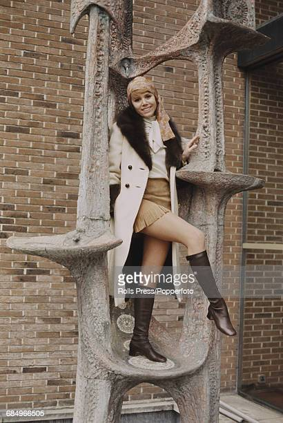 English actress Judy Carne who stars in the American television series 'Rowan Martin's LaughIn' posed standing on a sculpture in Elstree...