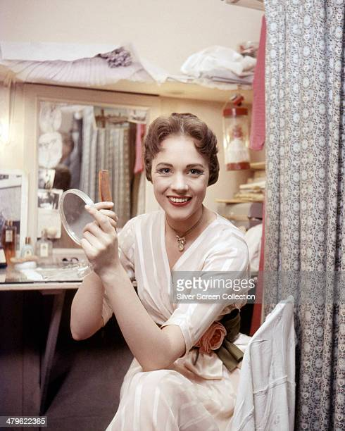 English actress Julie Andrews holding a hand mirror and a comb in a dressing room circa 1960