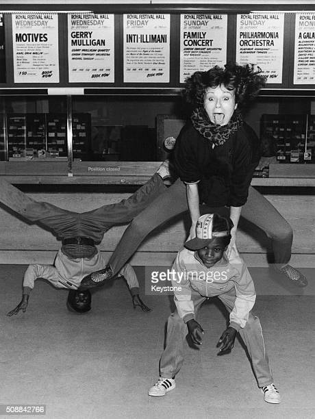 English actress Julie Walters playing leapfrog with two young breakdancers at the Royal Festival Hall London January 1985