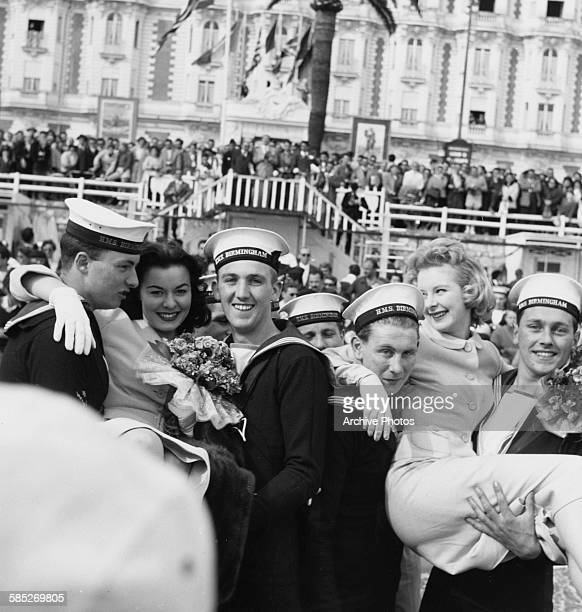 English actress June Laverick is lifted up by a group of Royal Navy sailors from the HMS Birmingham as the whole city comes out to greet them Cannes...