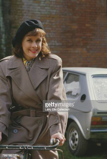 English actress Kirsten Cooke posed sitting on a bicycle in character as Michelle Dubois from the television sitcom series 'Allo 'Allo on location in...