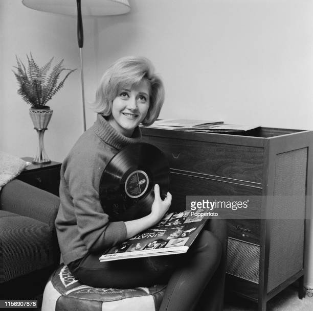 English actress Liz Fraser pictured holding a Frank Sinatra LP beside a music centre in her living room at home in March 1965