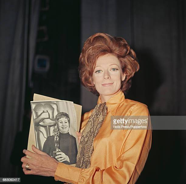 English actress Maggie Smith pictured holding a photograph of American actress Alice Ghostley accepting the Academy Award for Best Actress on behalf...