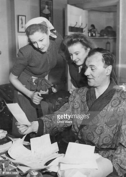 English actress Margaret Leighton and Diana Boddington stage manager of the Old Vic visit Sir Ralph Richardson as he reads congratulatory letters in...