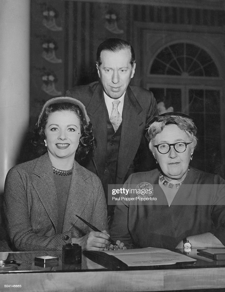 English actress Margaret Lockwood (1916 - 1990) (left) with English crime novelist, short story writer, and playwright Agatha Christie (1890 - 1976) and English theatre impresario Peter Saunders (1911 - 2003) as she signs the contract to star in Christie's play 'Spider's Web', London, 13th January 1954.