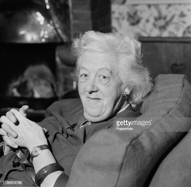 English actress Margaret Rutherford pictured seated on a sofa in January 1964