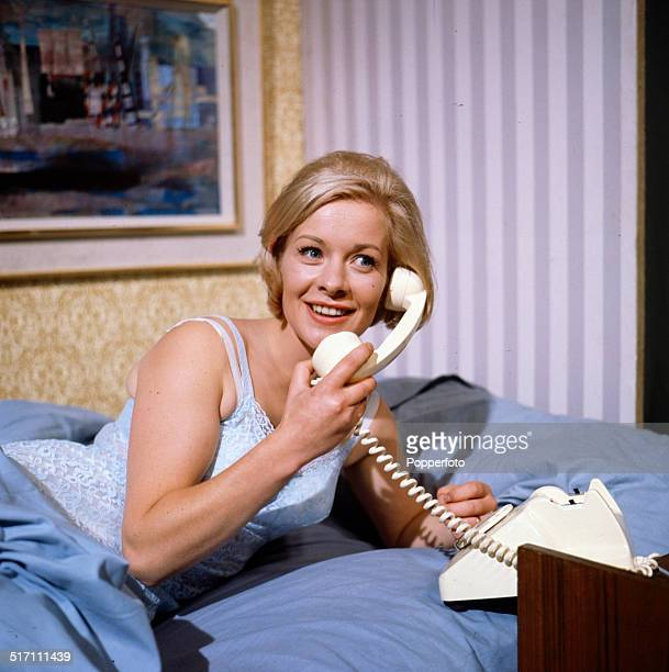 English actress Miranda Connell pictured holding a telephone receiver in a bedroom scene from the television drama 'The Hot House' in 1964