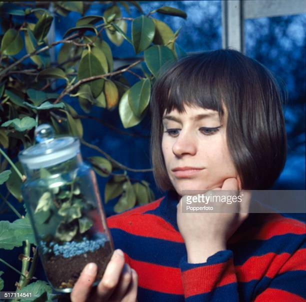 English actress Rita Tushingham posed holding a propogated plant cutting in a storage jar in 1965