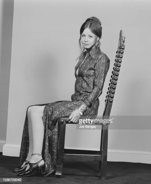 English actress Sarah Miles pictured wearing a full length shirt dress that she designed herself seated in a high backed wooden chair in England on...