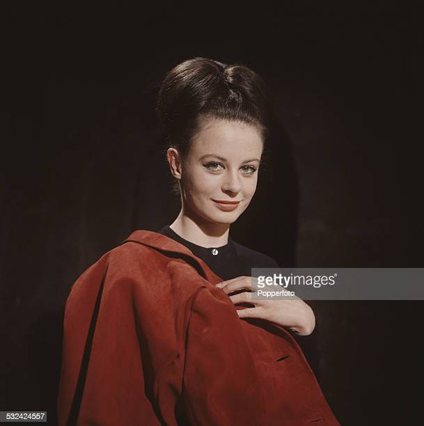 English actress Sarah Miles posed holding a red suede jacket draped over her shoulder in 1963