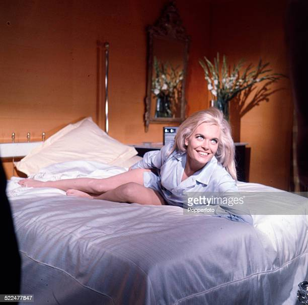 English actress Shirley Eaton in character as Jill Masterson lying on a bed wearing a light blue shirt on the set of the James Bond film 'Goldfinger'...
