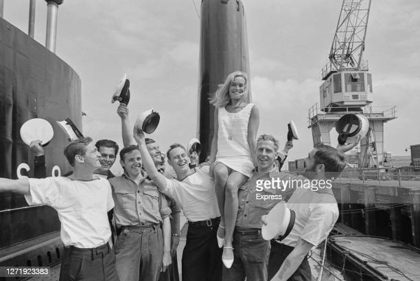 English actress Shirley Eaton meets the crew of the Royal Navy submarine 'HMS Grampus' at Plymouth, UK, 14th June 1966. She is publicising her latest...